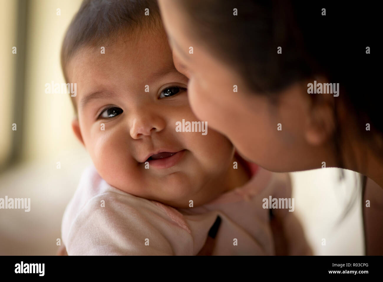 Young mother kisses her smiling baby daughter on the cheek. - Stock Image