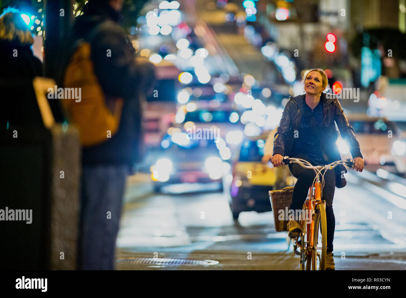 Smiling young woman riding her bicycle along a busy city road at night. Stock Photo