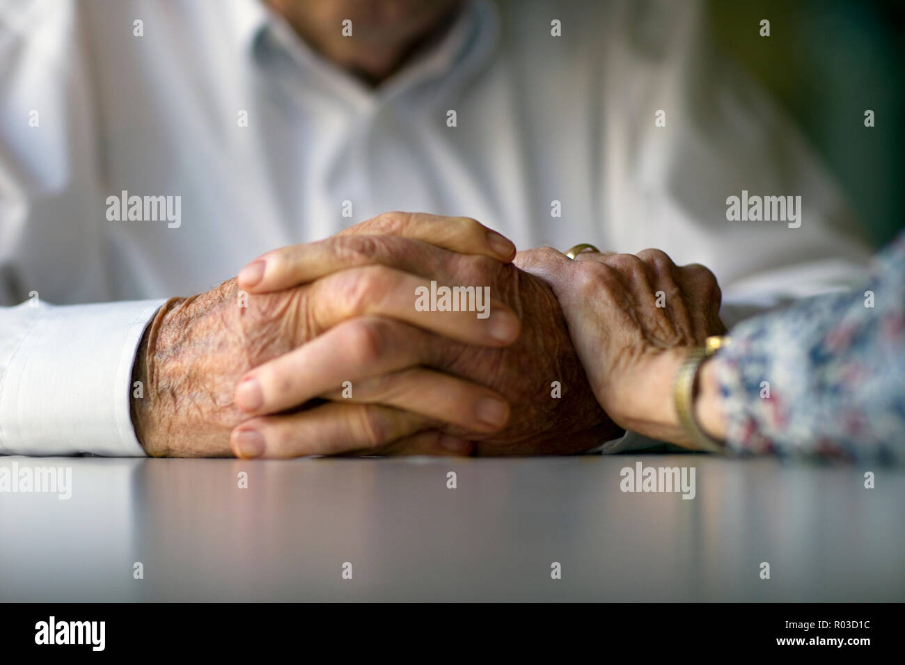 Elderly woman lays a comforting hand on her husband's arm. - Stock Image
