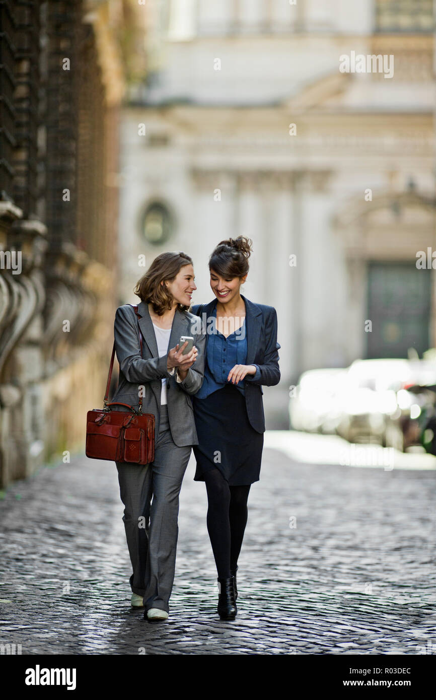 Two young women happily stroll at chat on the way home from the office. - Stock Image