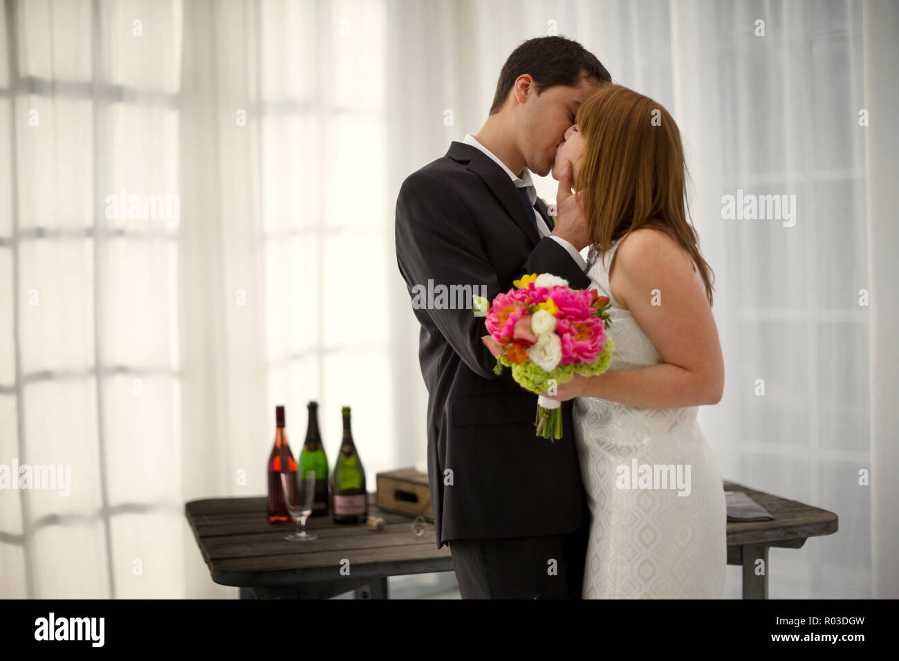 Bride and groom kissing at wedding reception. - Stock Image