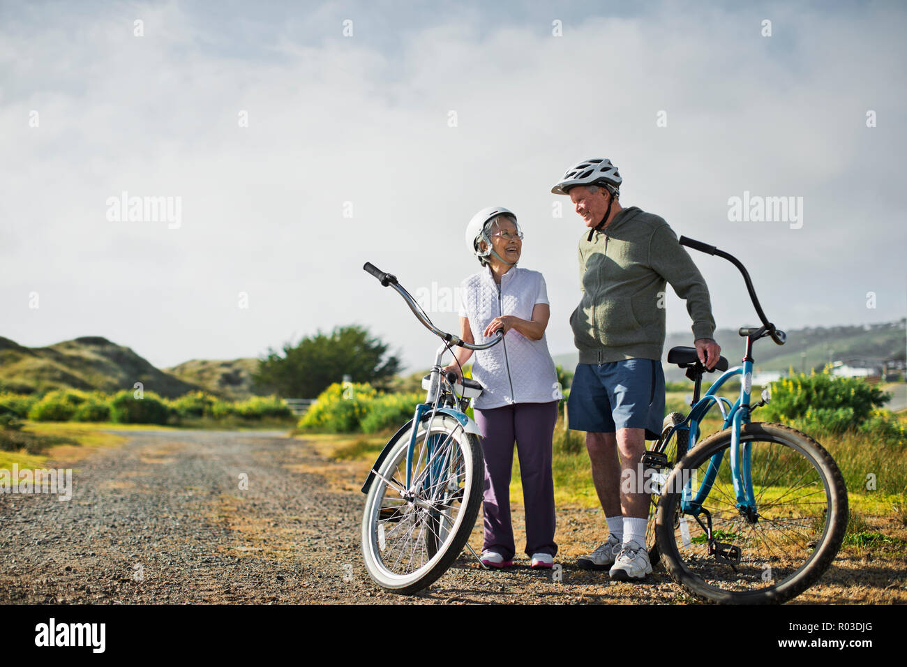 Happy elderly couple chat together as they take a break from biking along a country road. - Stock Image