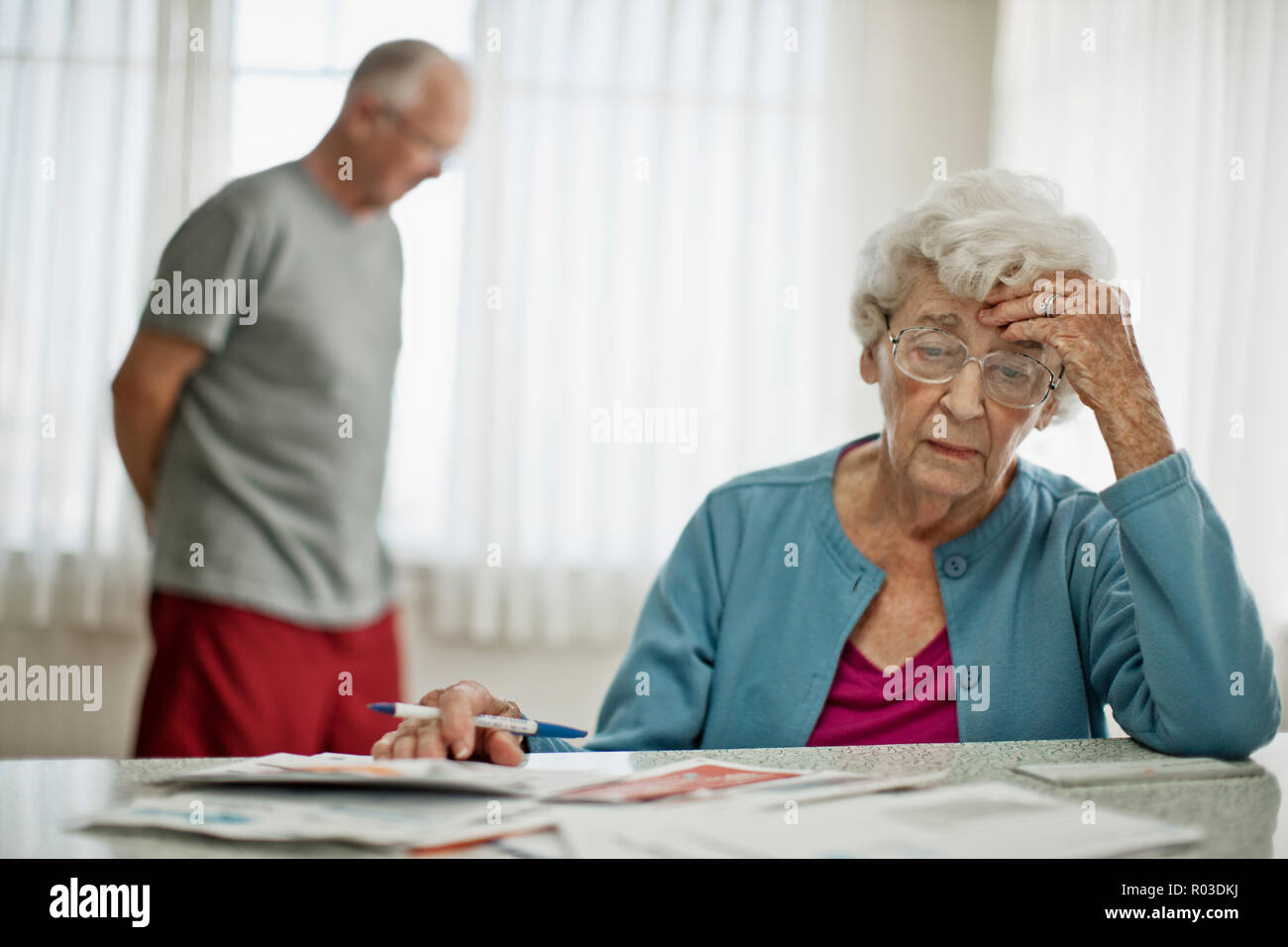 Anxious elderly couple worry about how they will pay all the bills they have received. - Stock Image