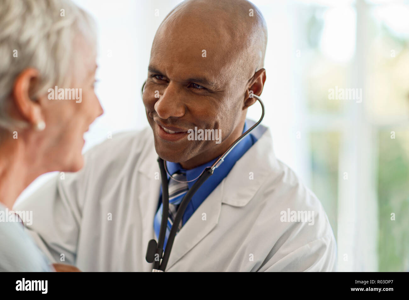 Mature woman gets her heartbeat checked by the doctor. - Stock Image