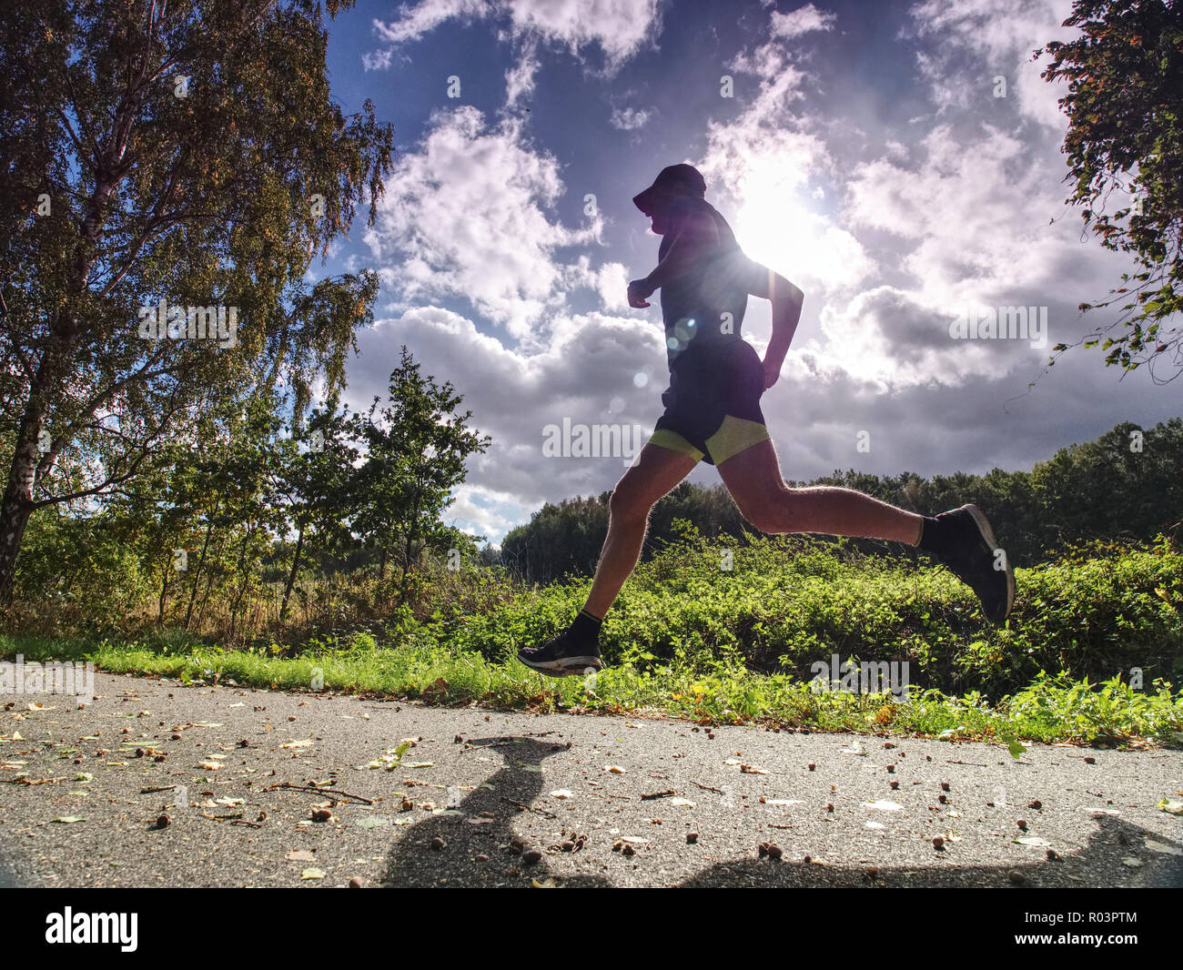 Jogging tall sports man in trees shadows with sun light behind him while wearing black yellow shorts and blue jogging attire Stock Photo