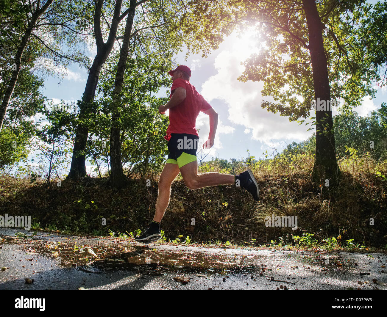 Man runner in yellow black shorts pants and red t-shirt is jumping over pool on asphalt road. Evening fitnes exercise in fall park - Stock Image