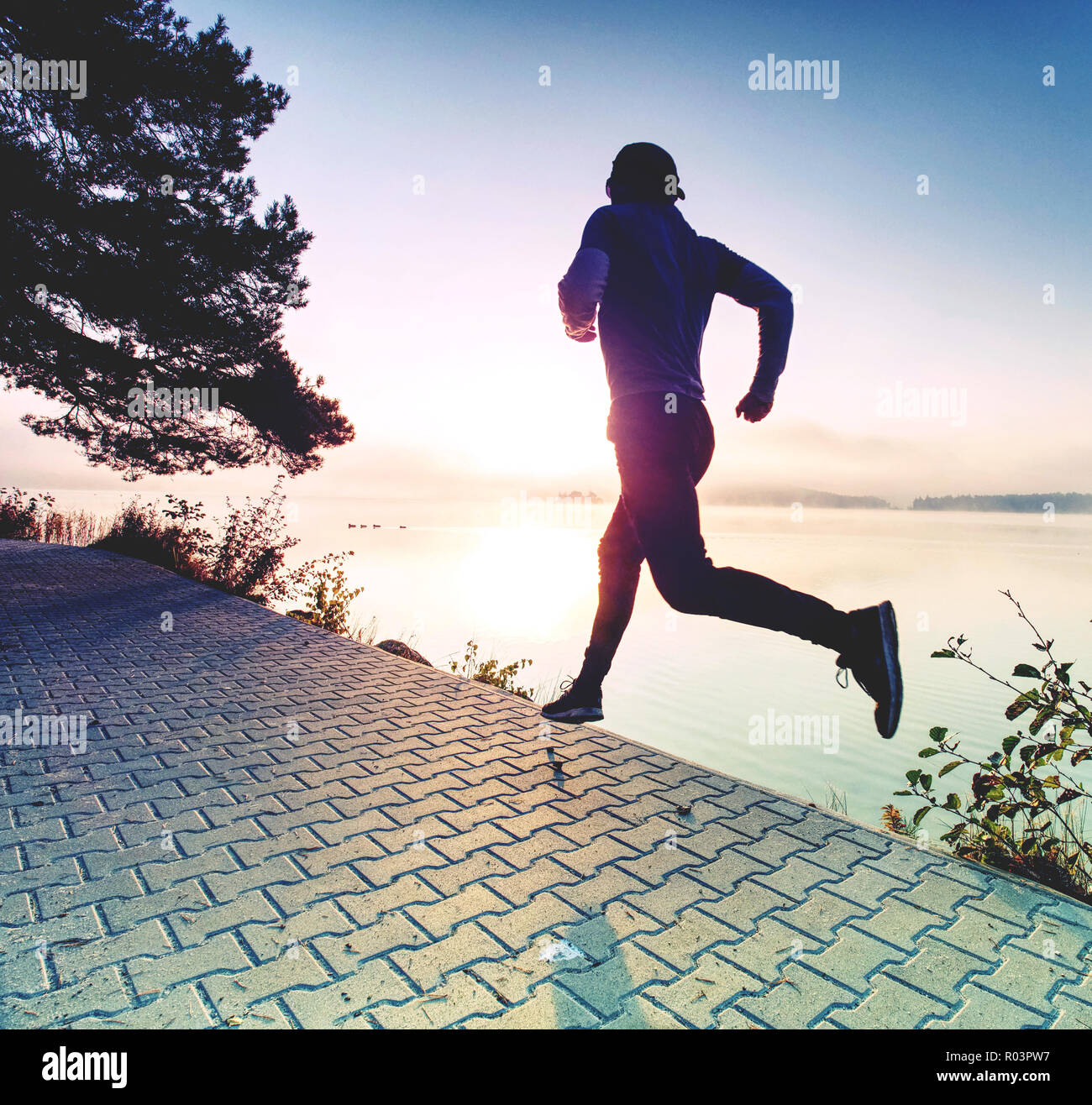 Man running on lake shore pavement during sunrise or sunset - healthy lifestyle concept - Stock Image