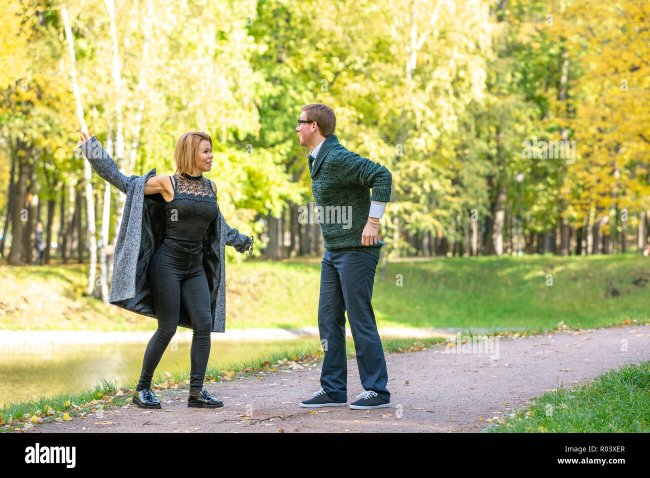 Couple talking seriously outdoors in a park with a green background Stock Photo