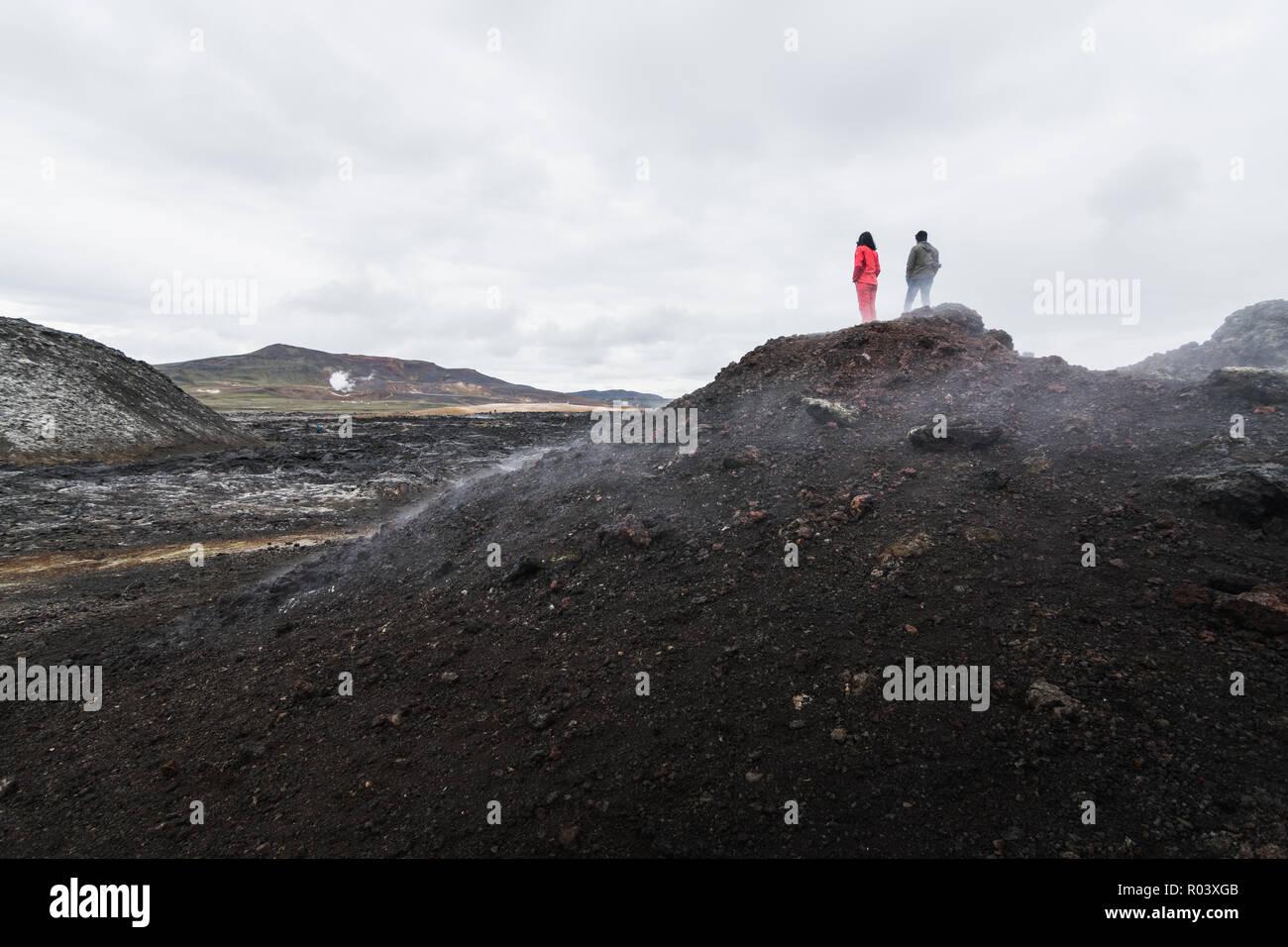 Woman and man figures standing in Krafla volcano lava field around Leirhnjukur mountain peak, Iceland. - Stock Image
