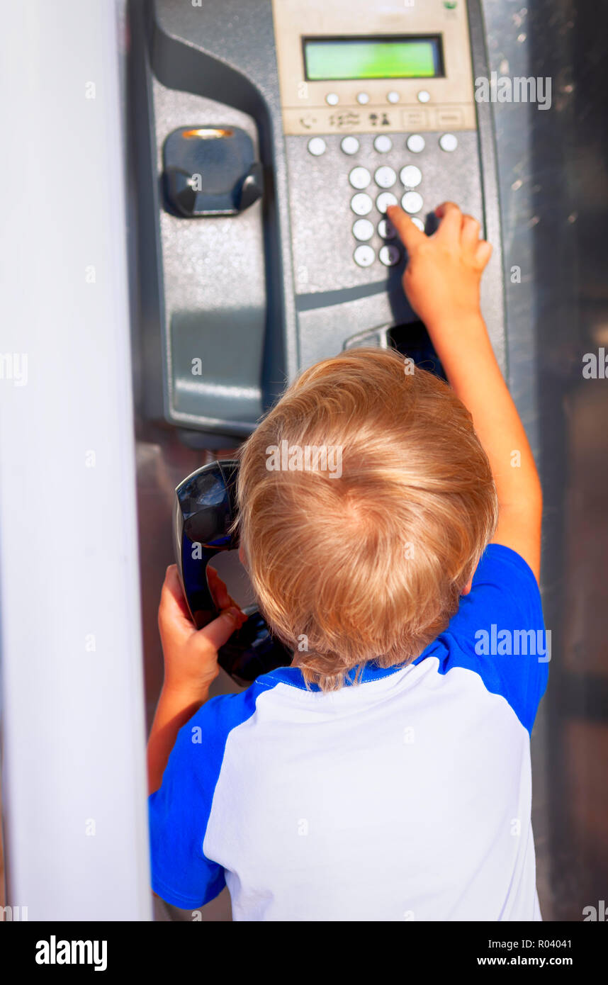 Kid dialing up a number on payphone. - Stock Image