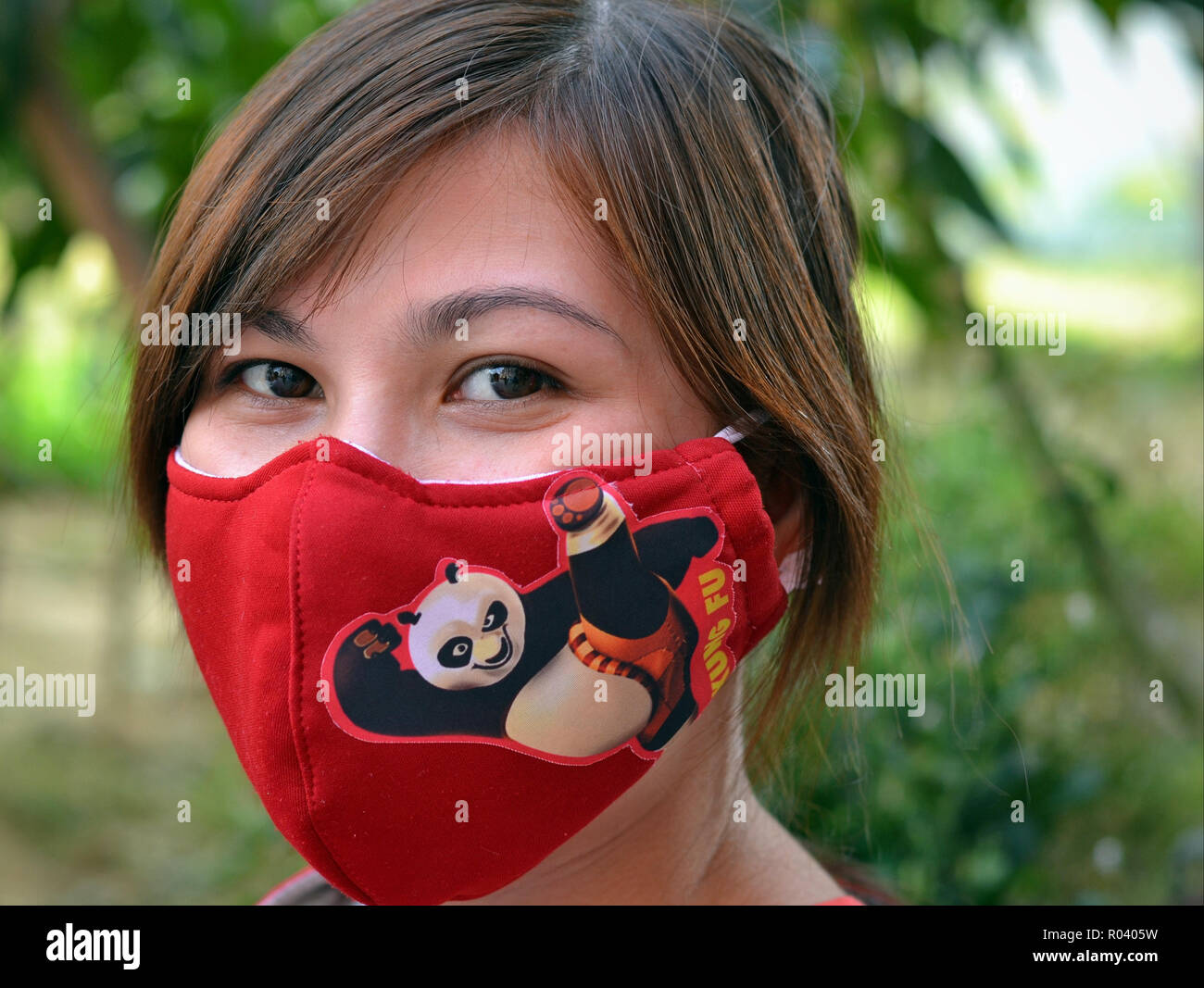 Young Taiwanese woman with beautiful oriental eyes wears a red washable protective earlobe face mask depicting the Kung Fu Panda. - Stock Image