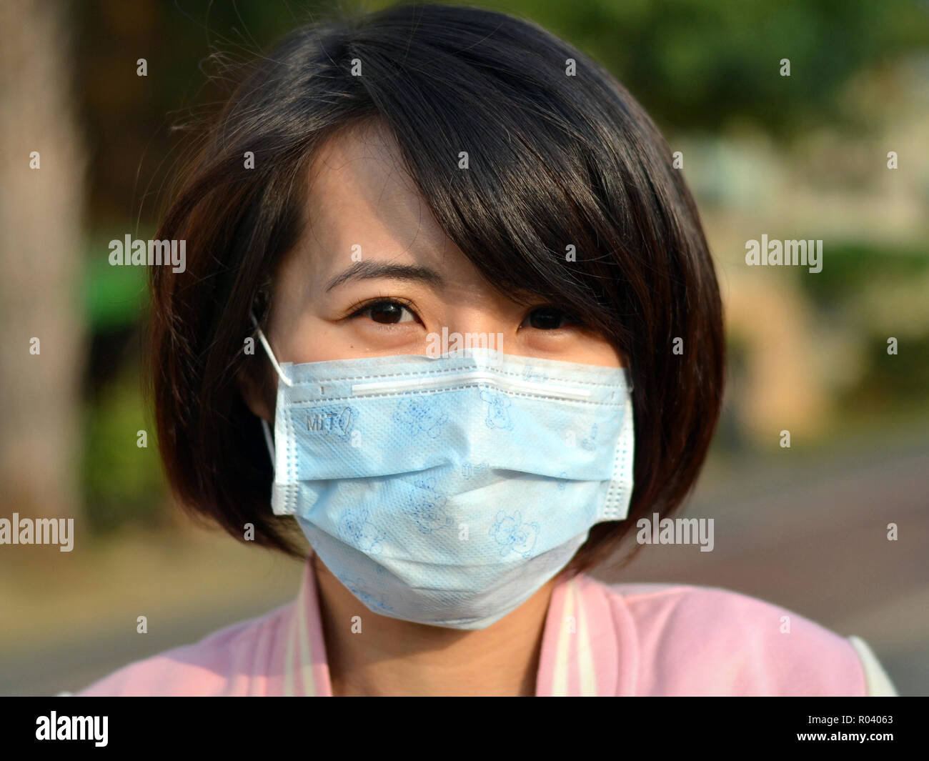 Young Taiwanese woman with beautiful oriental eyes wears a light-blue disposable surgical earlobe face mask. - Stock Image