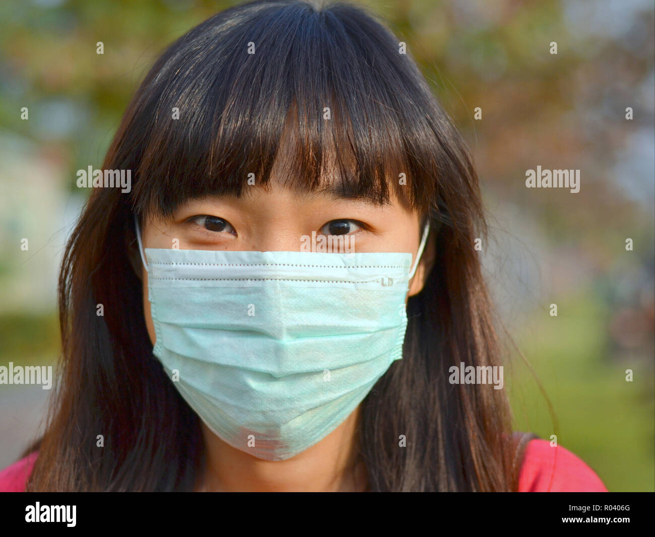 Young Taiwanese woman with beautiful oriental eyes wears a light-green disposable surgical face mask. - Stock Image
