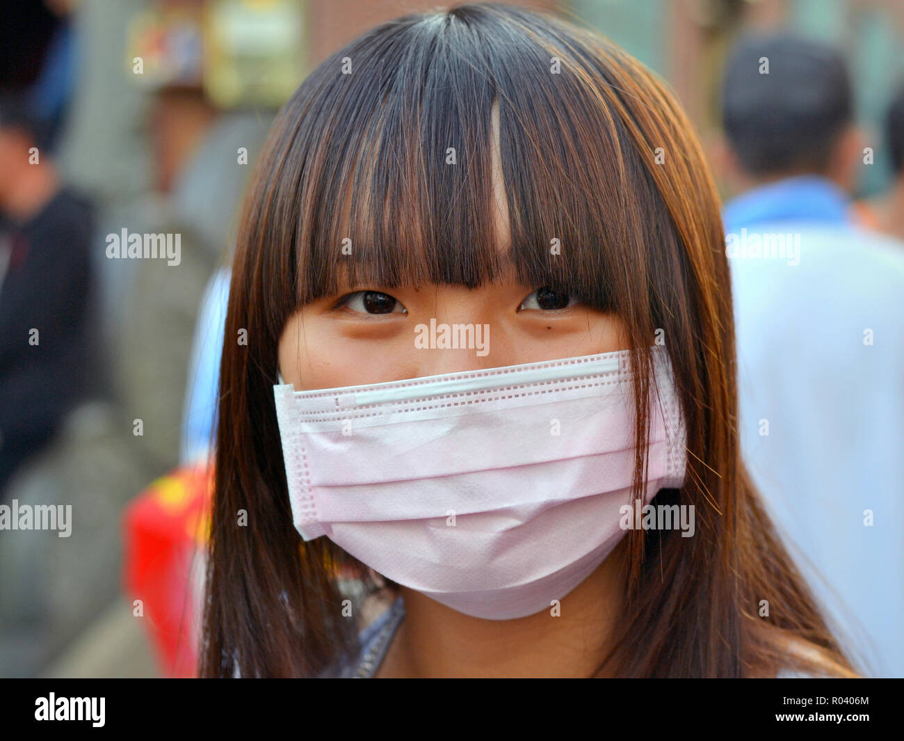Young Taiwanese woman with beautiful oriental eyes and fringe wears a pink disposable surgical earlobe face mask. - Stock Image