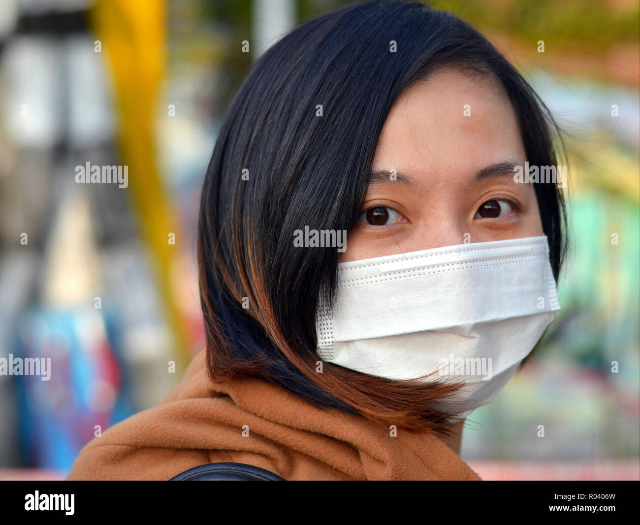 Young Taiwanese woman with big eyes wears in public a white disposable surgical earlobe face mask. - Stock Image