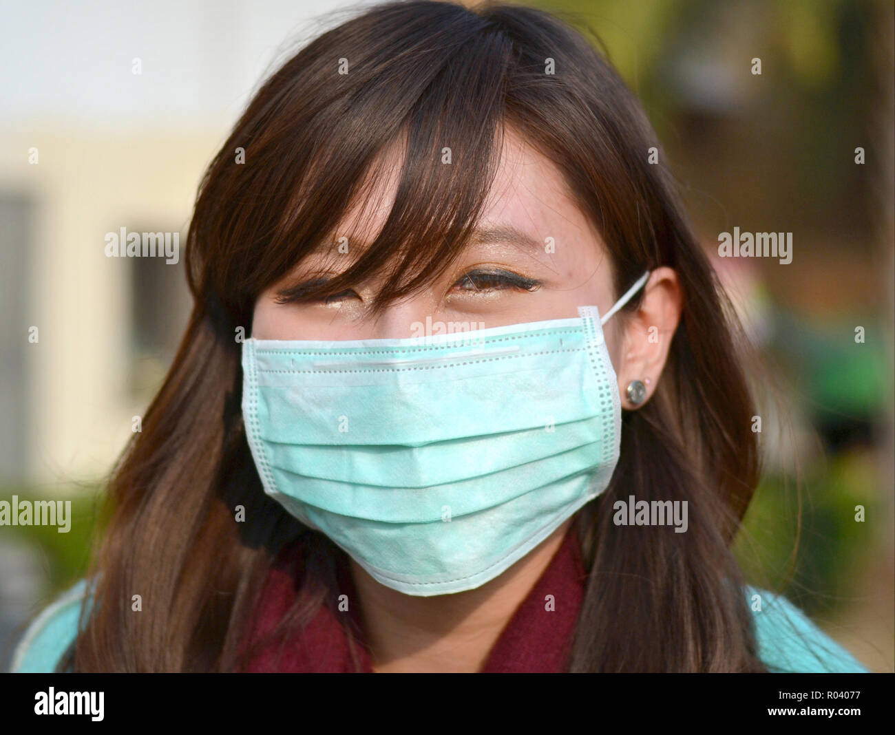 Young Taiwanese woman with oriental eyes wears a light-green disposable surgical earlobe face mask. - Stock Image