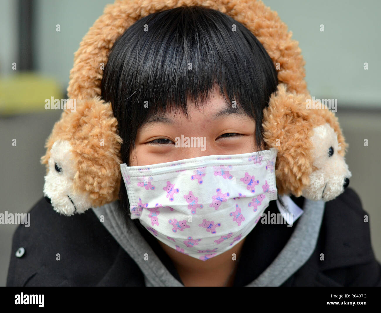 Young Taiwanese woman with smiling eyes wears a disposable surgical earlobe face mask and fluffy winter earmuffs. - Stock Image