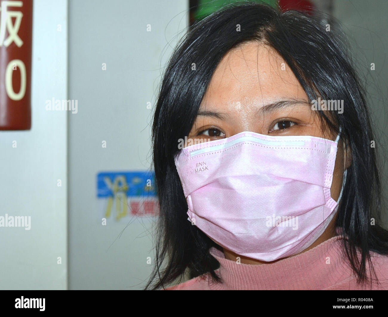 Young Taiwanese vegetarian cookee and waitress with smiling eyes wears a pink disposable surgical earlobe face mask. - Stock Image