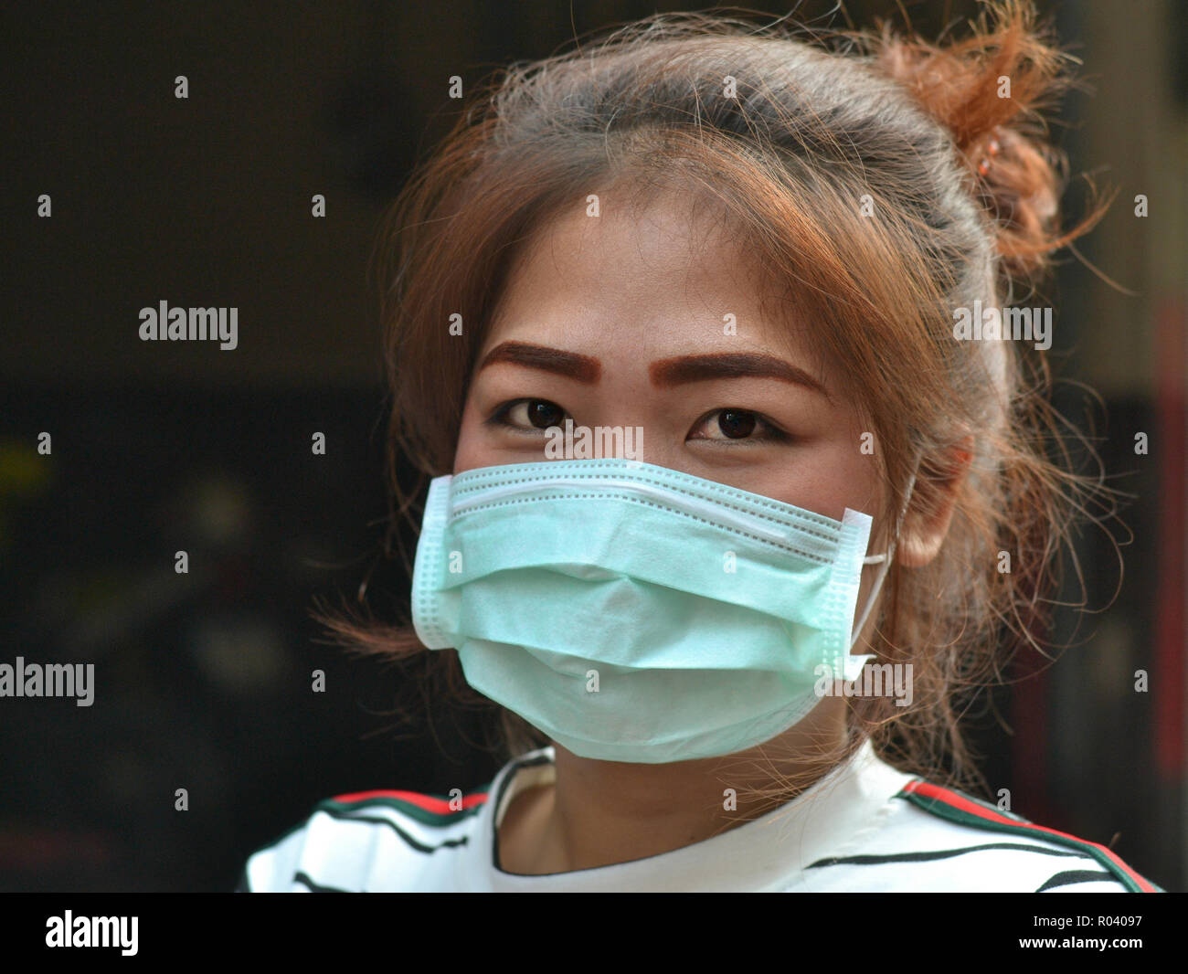 Young Thai Chinese woman with beautiful eyes wears a disposable surgical earlobe face mask. - Stock Image