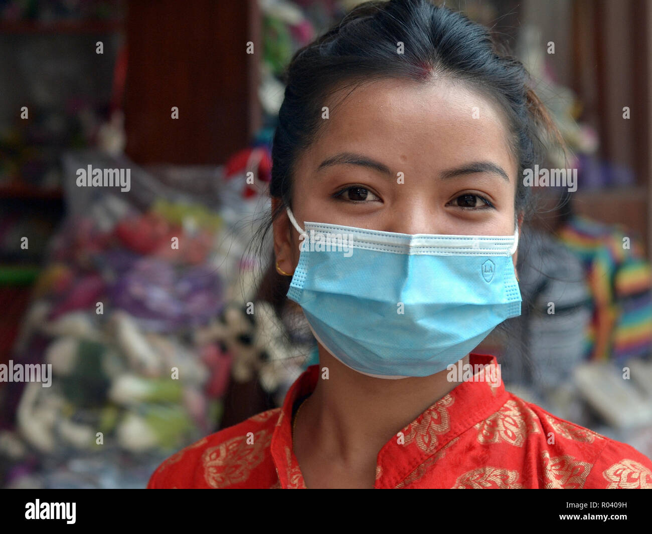 Young Nepali woman with beautiful eyes wears a light-blue disposable surgical earlobe face mask to protect herself against Kathmandu's air pollution. - Stock Image