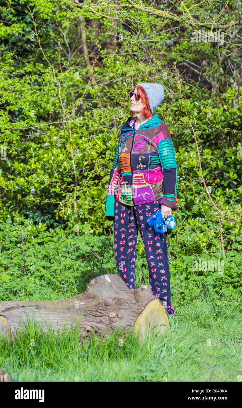 Senior woman standing in woodland looking up smiling, wearing cool looking younger persons multicoloured clothing. - Stock Image