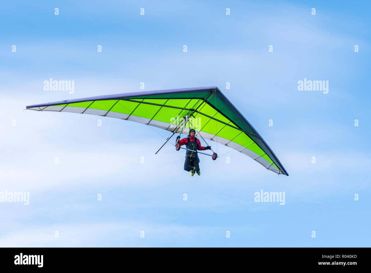 Man hang gliding in Autumn with blue sky, looking for a place to land on the South Downs in East Sussex, England, UK. - Stock Image