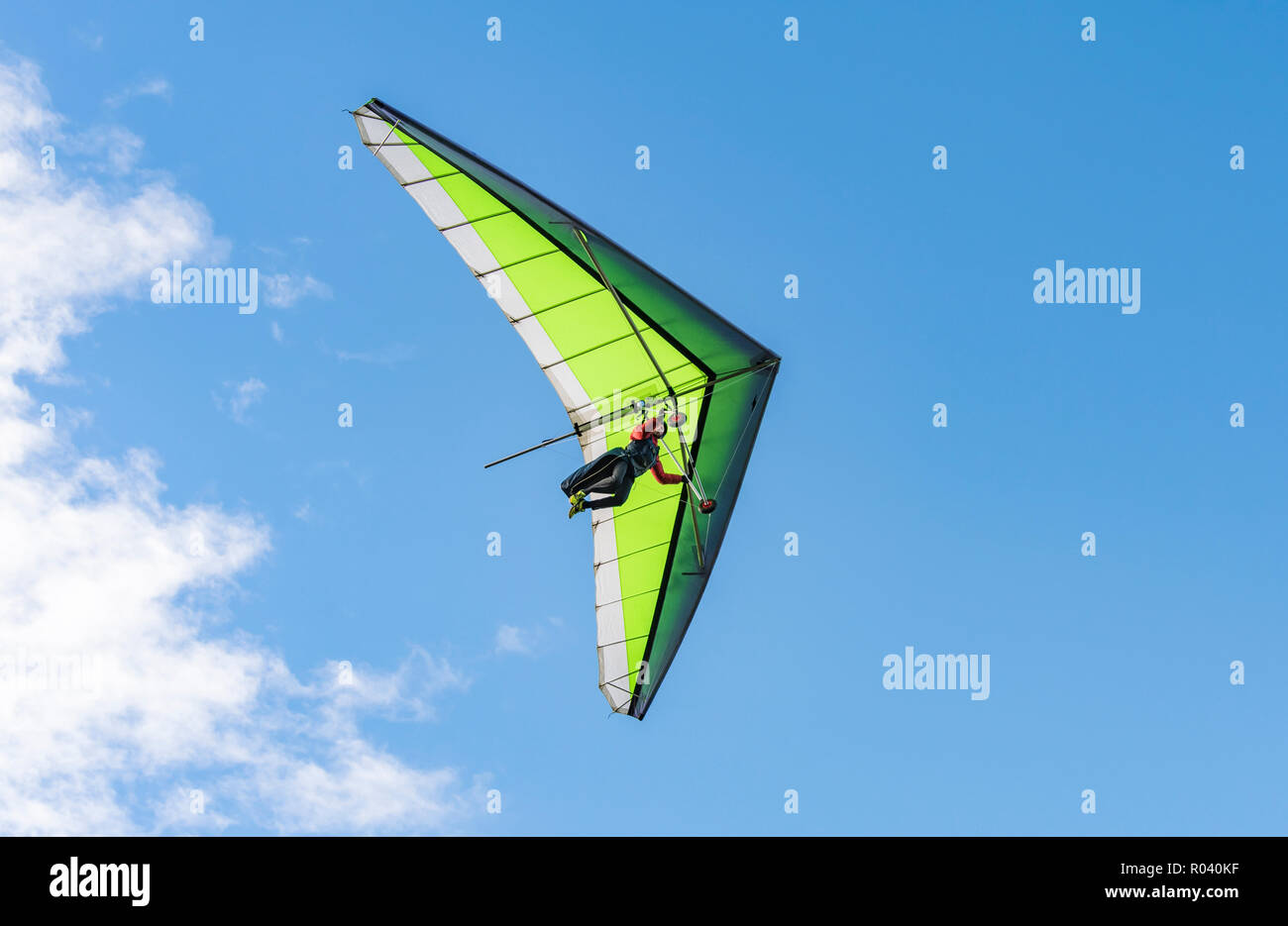 Man hang gliding in Autumn with blue sky at the South Downs in East Sussex, England, UK. - Stock Image