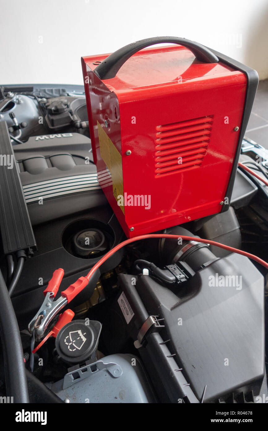 Car engine space with bonnet up and battery on charge with broken down car - Stock Image
