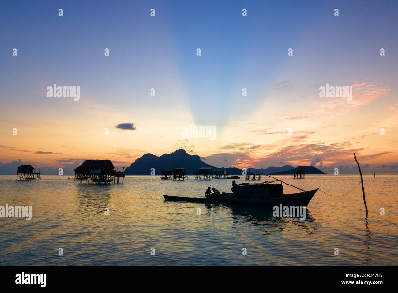 Beautiful sunrise with boat and house built stilt on water at Maiga Island Semporna Sabah - Stock Image