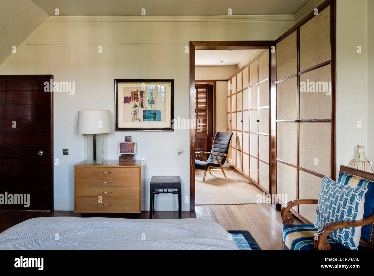 Drawers and armchairs in bedroom - Stock Image
