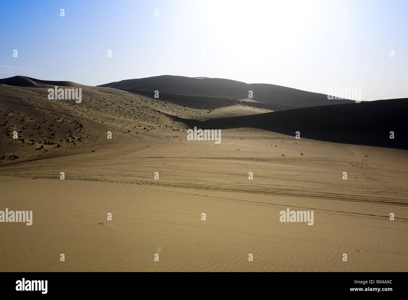 Desert sand dunes with blue sky background - Stock Image