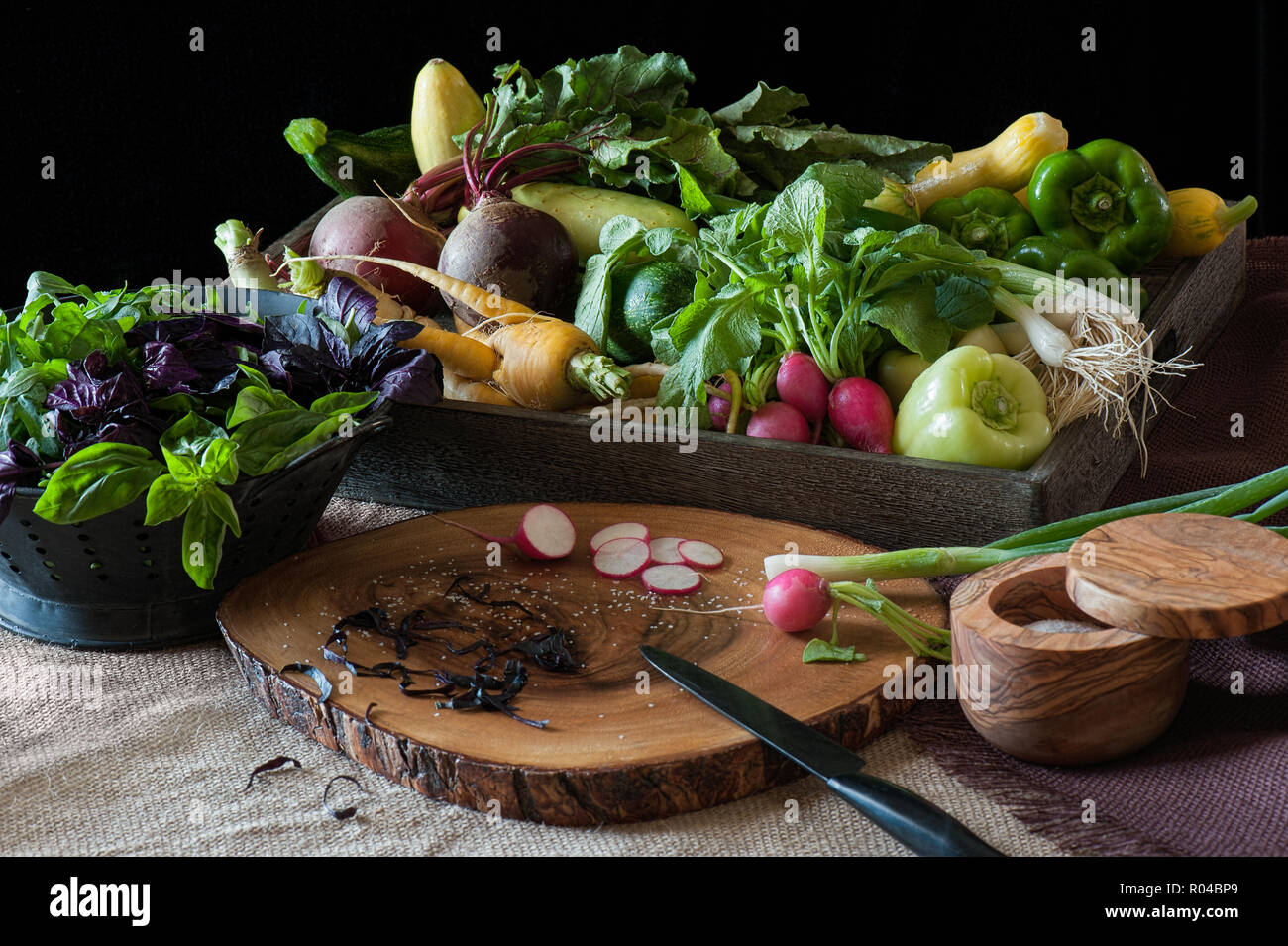 Farm-fresh produce in a kitchen scene complete with wood cutting board and salt ewer. Stock Photo