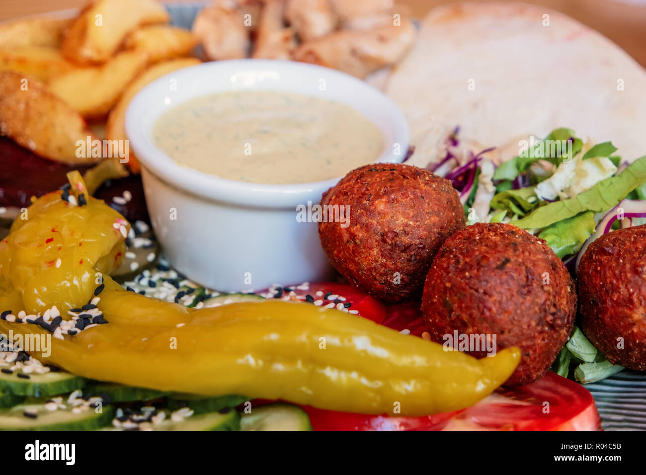 Dish with falafel, pepper and vegetables mix with bowl of souse in the center - Stock Image