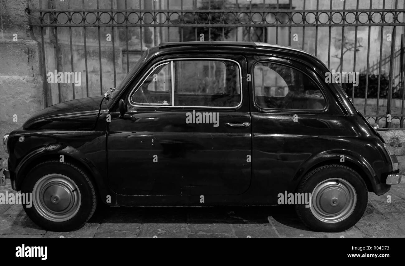 Lecce, Ital. Black Fiat vintage cinquecento 500 car parked in front of railings outside church in Puglia, Southern Italy. - Stock Image