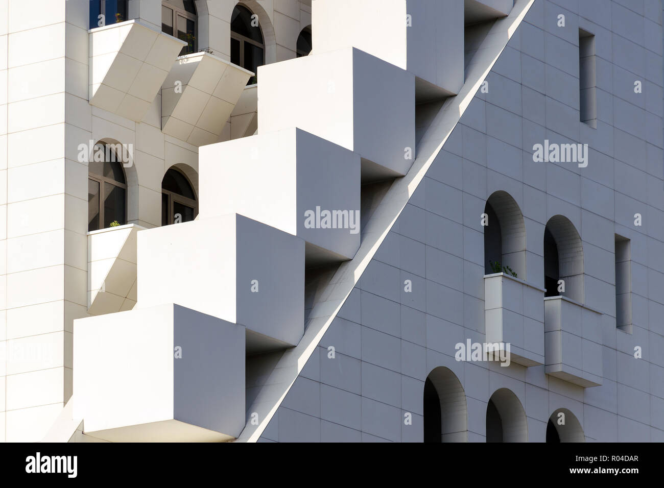 Mixing of forms and shapes, layering in modern architecture - part of facade building, unusual geometrical exterior, complex structure. Stock Photo