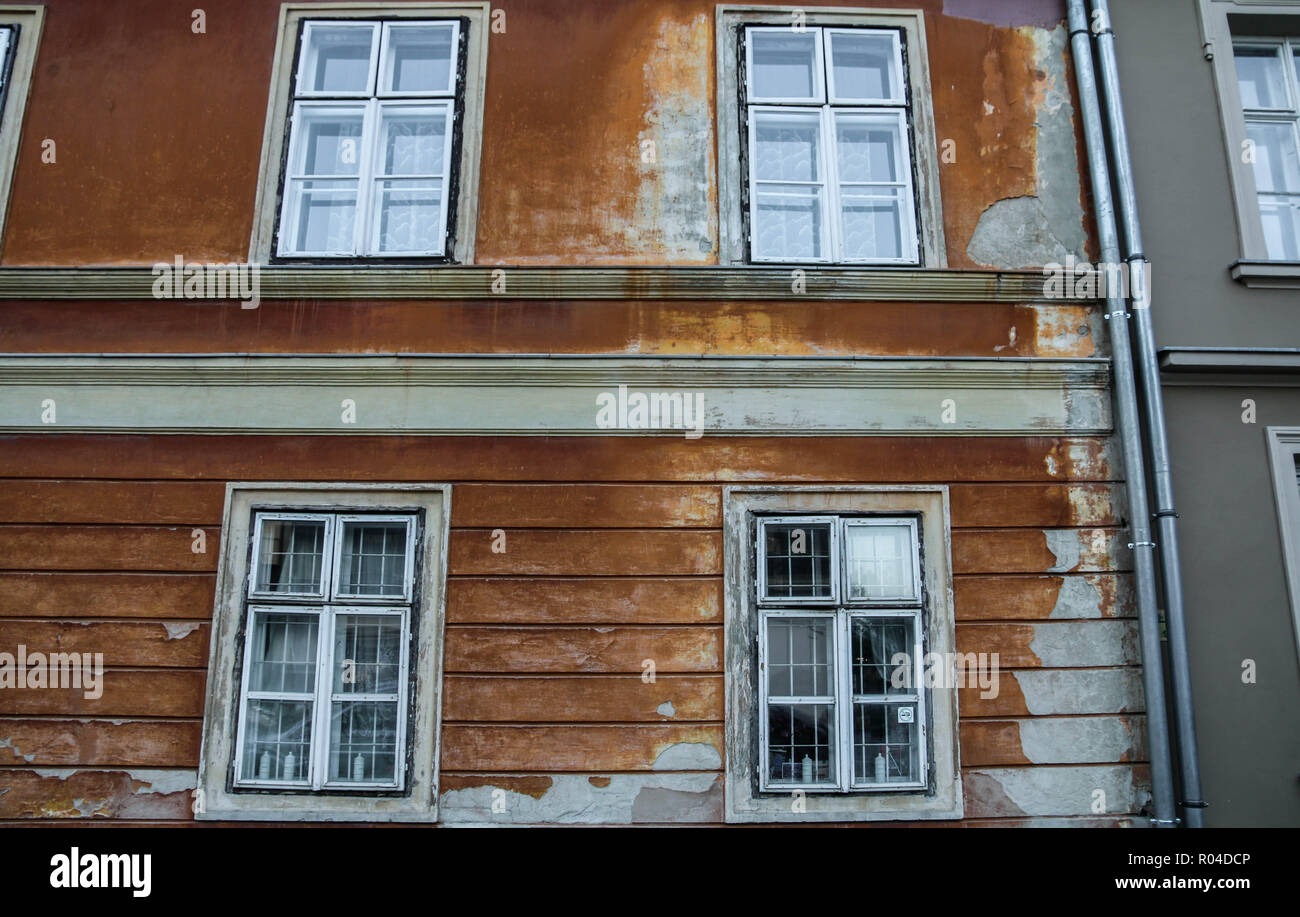 Reddish-brown old brick wall with white windows frame at Buda castle, Budapest, Hungary. - Stock Image