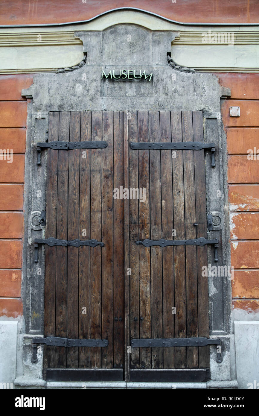 Old brown wood double closed Museum door with reddish brown brick walls around it at Buda castle, Budapest, Hungary - Stock Image
