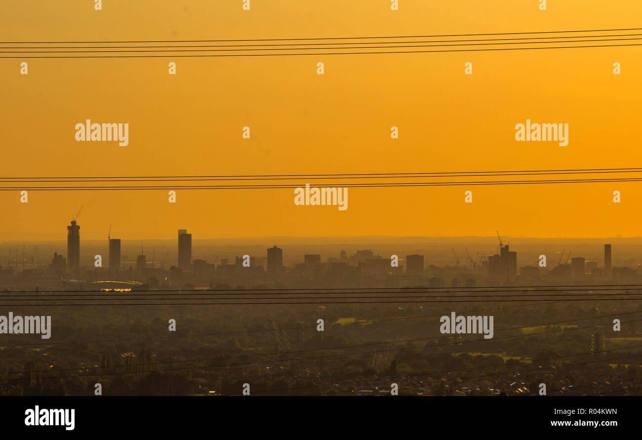 The sky appears yellow as the sun sets over Greater Manchester on a misty evening - Stock Image