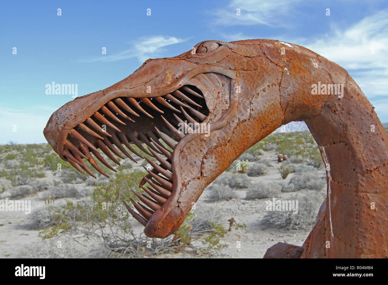 metal sculpture of raptor dinosaur head with multiple teeth