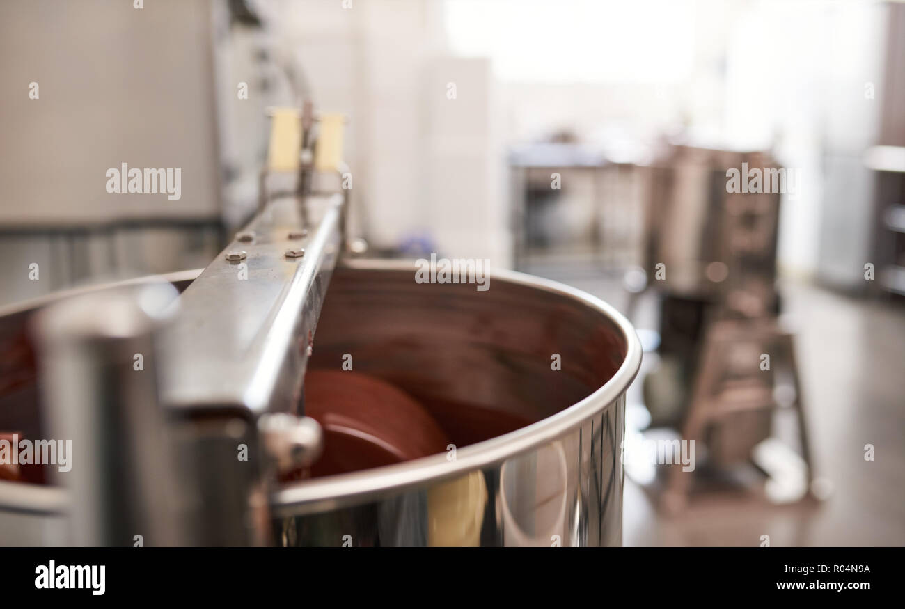 Stainless steel mixer stirring melted chocolate in an artisanal workshop - Stock Image