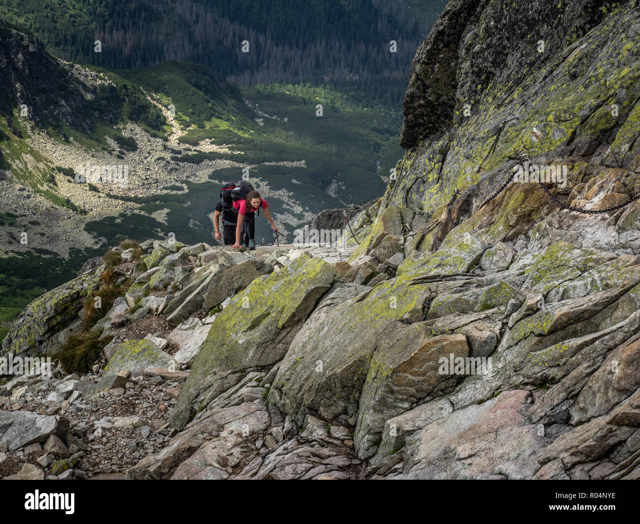 Lady scrambling on Swinica, 2301m, using metal chains, on the Polish and Slovak border in the Tatra Mountains, Poland, Europe - Stock Image