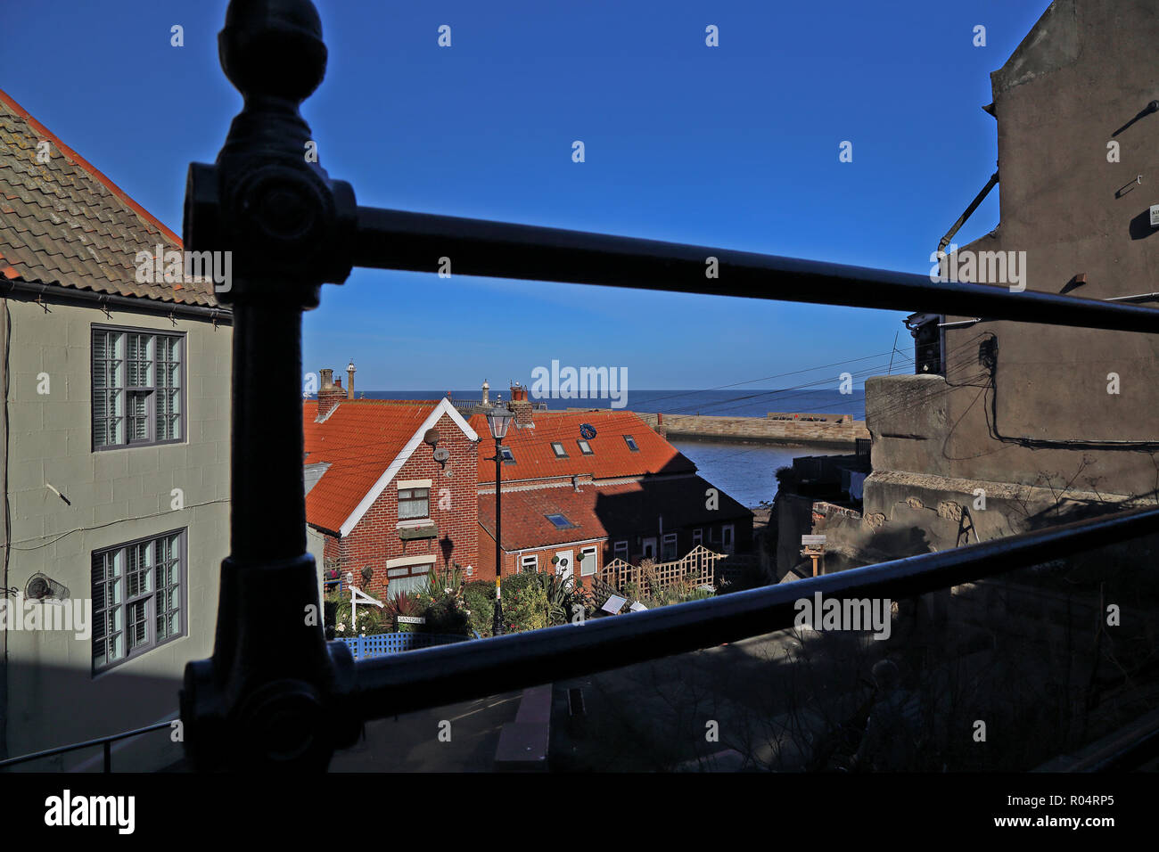 A view of Whitby and the harbour through railings from Church Lane at the bottom of St Mary's steps on a bright autumn day with blue cloudless sky. - Stock Image