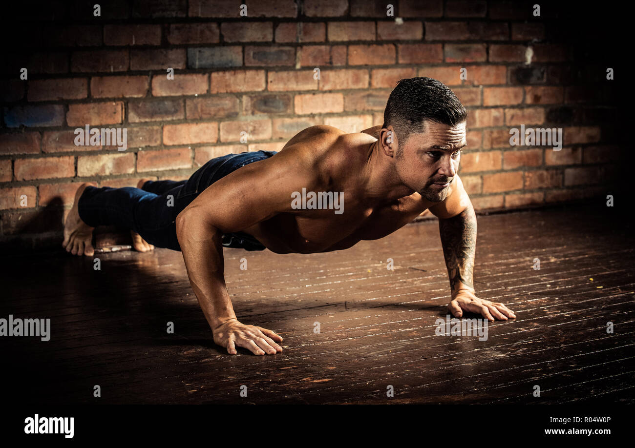 Muscular male engaged in cross fit training and performing push-ups. - Stock Image
