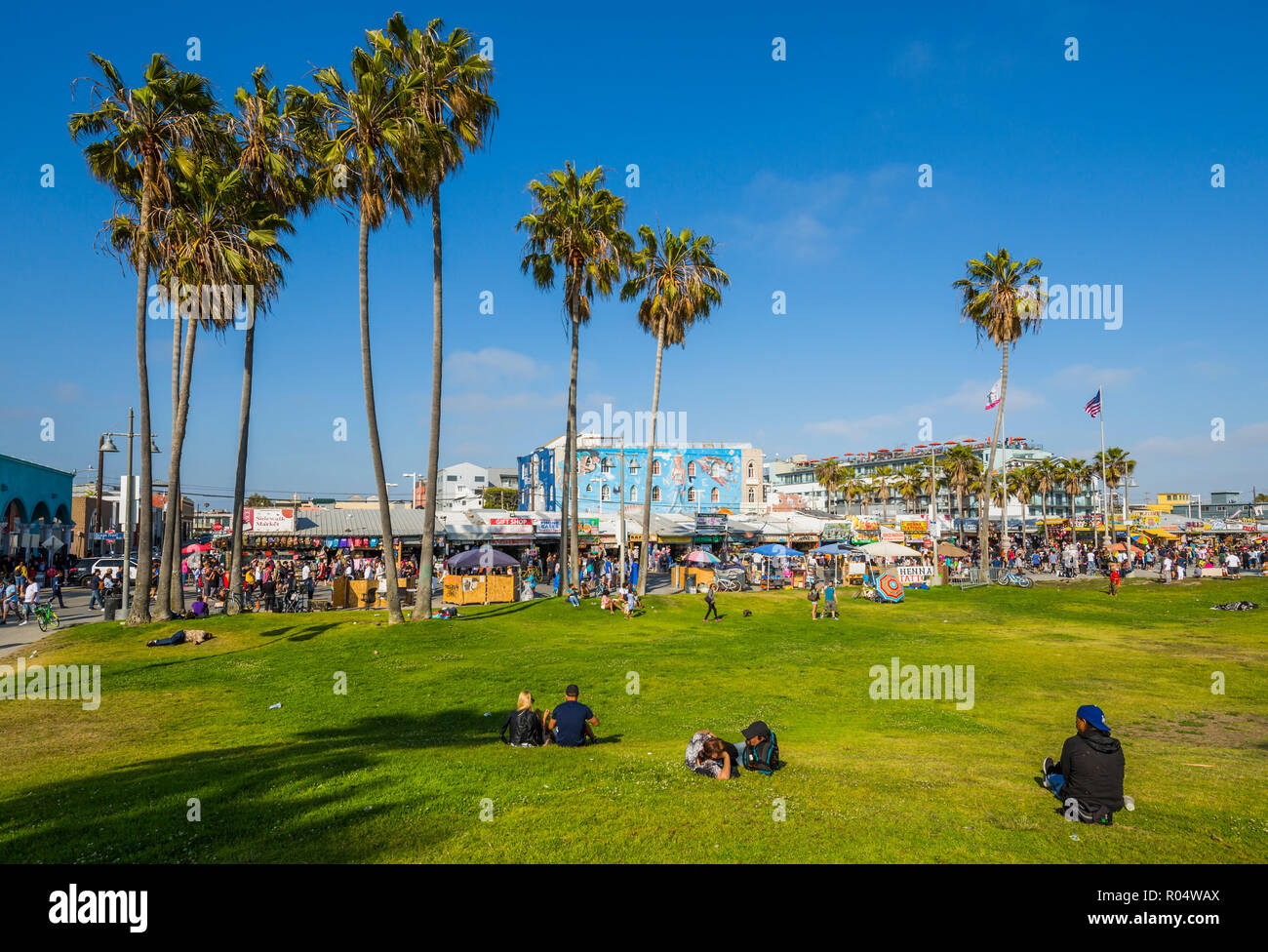 View of palm trees and visitors on Ocean Front Walk in Venice Beach, Los Angeles, California, United States of America, North America Stock Photo