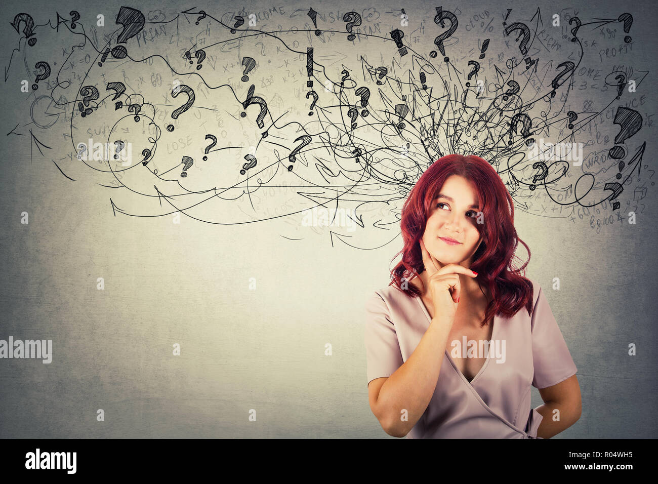 Young redhead pensive woman having questions holding hand under chin thoughtful looking at arrows and mess going out of head. - Stock Image
