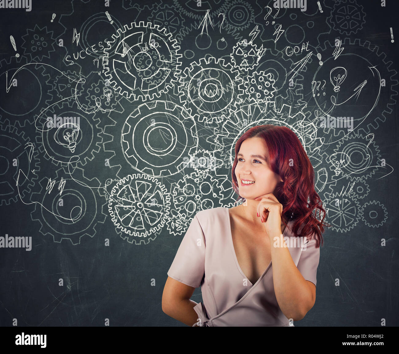 Hard thinking serious smart woman over blackboard background gear brain arrows and mess as thoughts. Concept for mental, psychological development. Fi - Stock Image