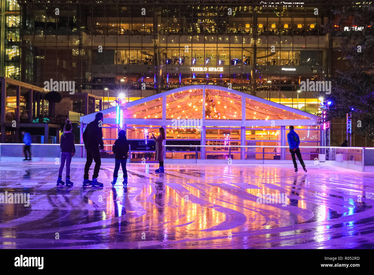 Canary Wharf, London, UK, 1st Nov 2018. Skaters on the ice. The Canary Wharf ice rink 2018 is launched with a party on the winter terrace and skate session. The ice rink is the only one in London with a 40 sq, metre LED screen, providing a colourful backdrop skaters can upload photos to. Credit: Imageplotter News and Sports/Alamy Live News Stock Photo