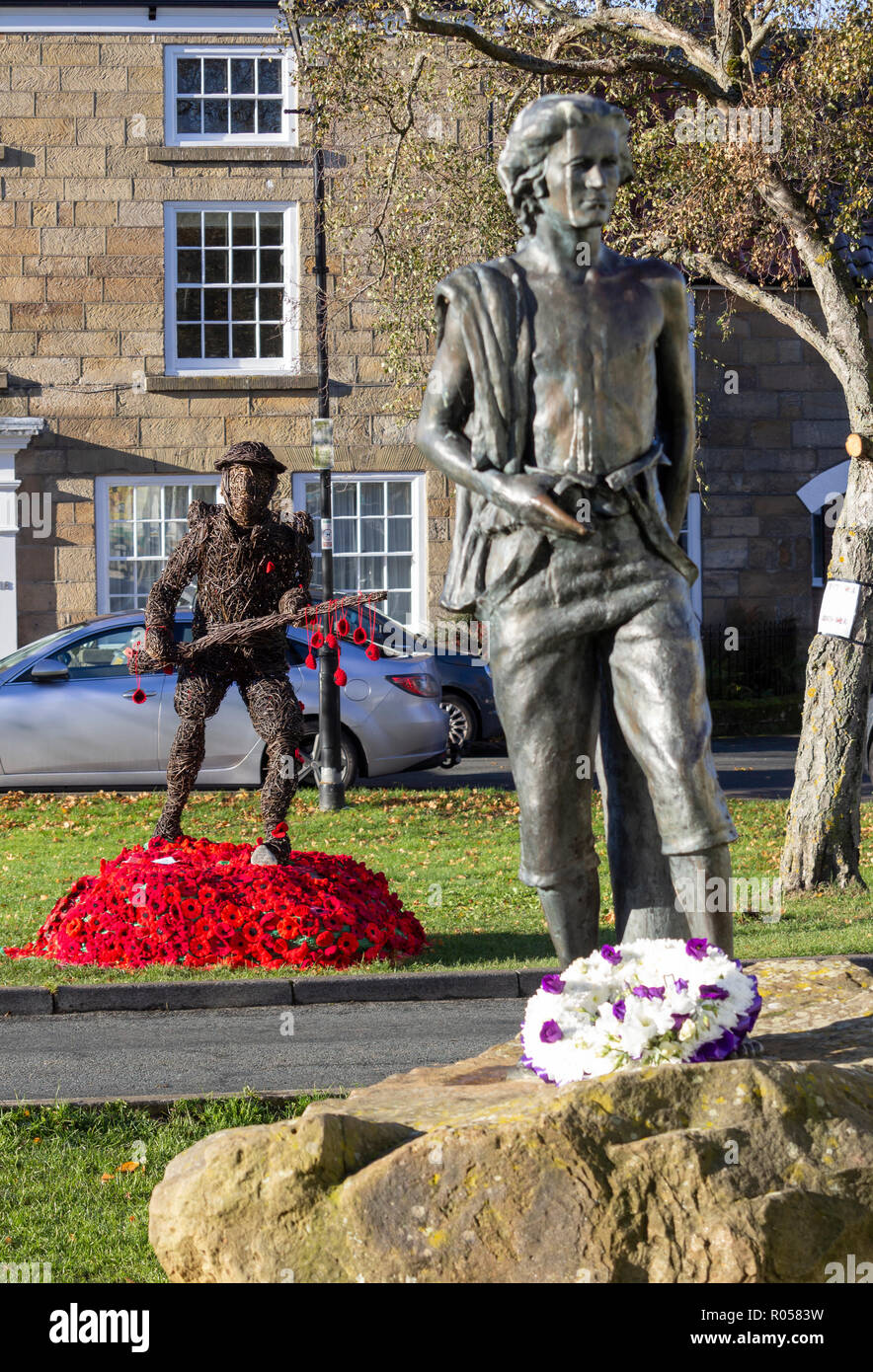 Great Ayton village,The North York Moors National Park, North Yorkshire, England, United Kingdom. 2nd November 2018. Knitted poppies around Willow sculpture of First World War soldier in Grear Ayton village, North Yorkshire on a clear and frosty morning. The sculpture is in remembrance to the men and women of the village who served during The Great War. Off the 260 who went off to war, only 50 returned. Great Ayton was the childhood home of Captain James Cook. Sculpture in foreground is a young James Cook. Credit: ALAN DAWSON/Alamy Live News - Stock Image