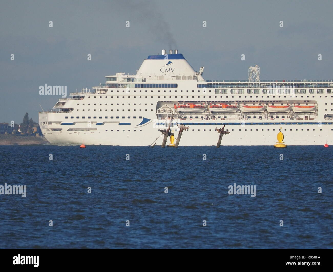Sheerness, Kent, UK. 2nd Nov, 2018. Cruise ship 'Columbus' passing the masts of the SS Richard Montgomery off Sheerness on a sunny afternoon. Columbus is 246m long by 32m wide and was built in 1988.  Credit: James Bell/Alamy Live News - Stock Image