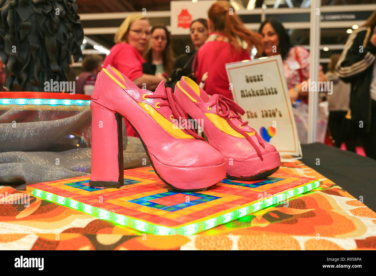 Birmingham, UK. 2nd November, 2018. The opening day of the 25th Cake International Show at the NEC in Birmingham. Hundreds of exhibitors show off their skills in sugar and cake. Nostalgia for the 1970s is shown in a pair of ourageous platform shoes.  Peter Lopeman/Alamy Live News - Stock Image